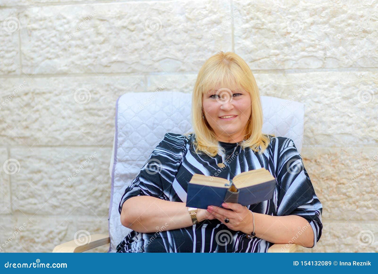 Mooie middenleeftijd die Skandinavische vrouw in openlucht het boekzitting van de terraslezing glimlachen in leunstoel