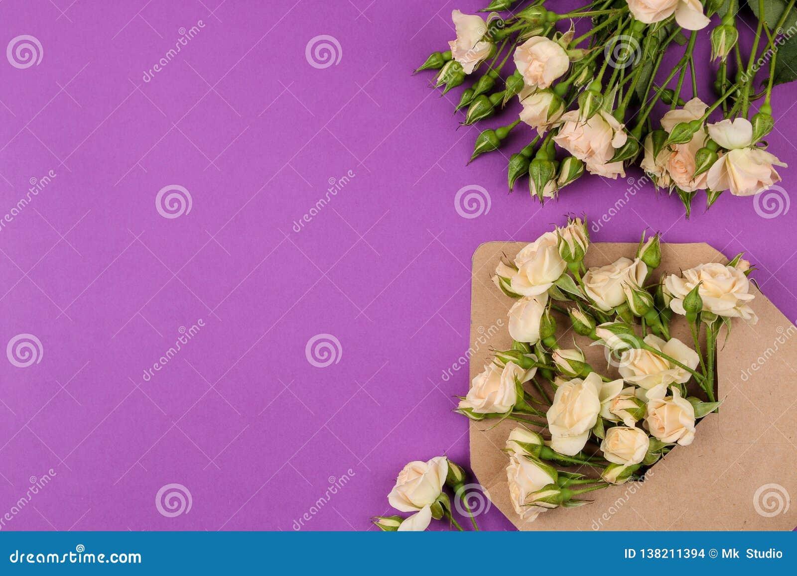 Mooie minirozen in envelop met blocnote op een heldere lilac achtergrond vakantie De dag van de valentijnskaart `s De dag van vro