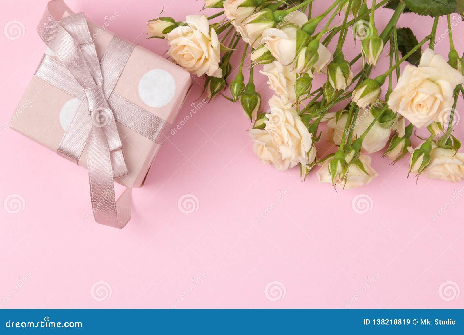Mooie minirozen met een roze giftdoos op een heldere roze achtergrond vakantie De dag van de valentijnskaart `s De dag van vrouwe