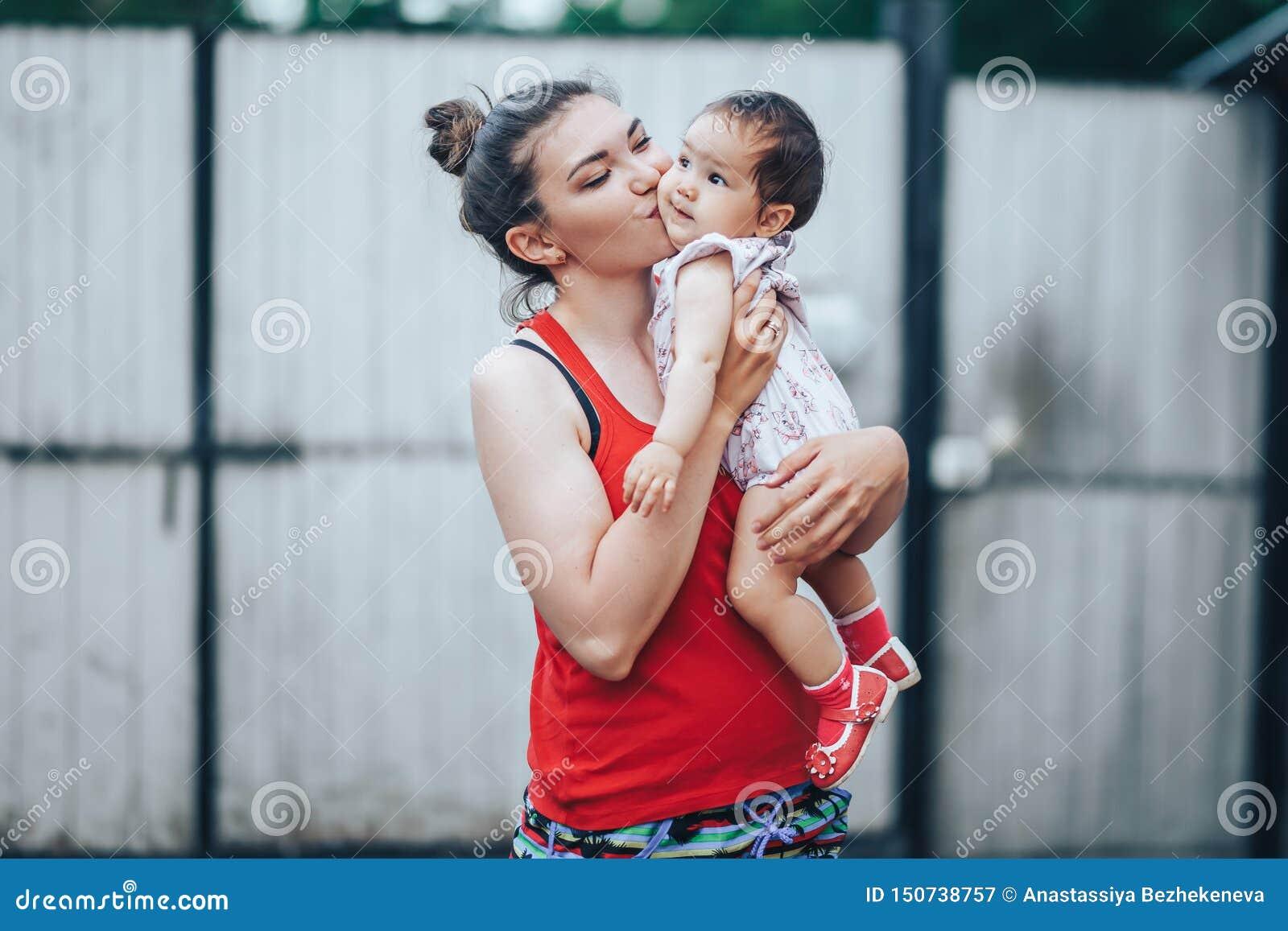 Mooie Moeder en Baby in openlucht op de yard van huis Schoonheid Mum en haar babykind één éénjarige die in yard samen spelen mom