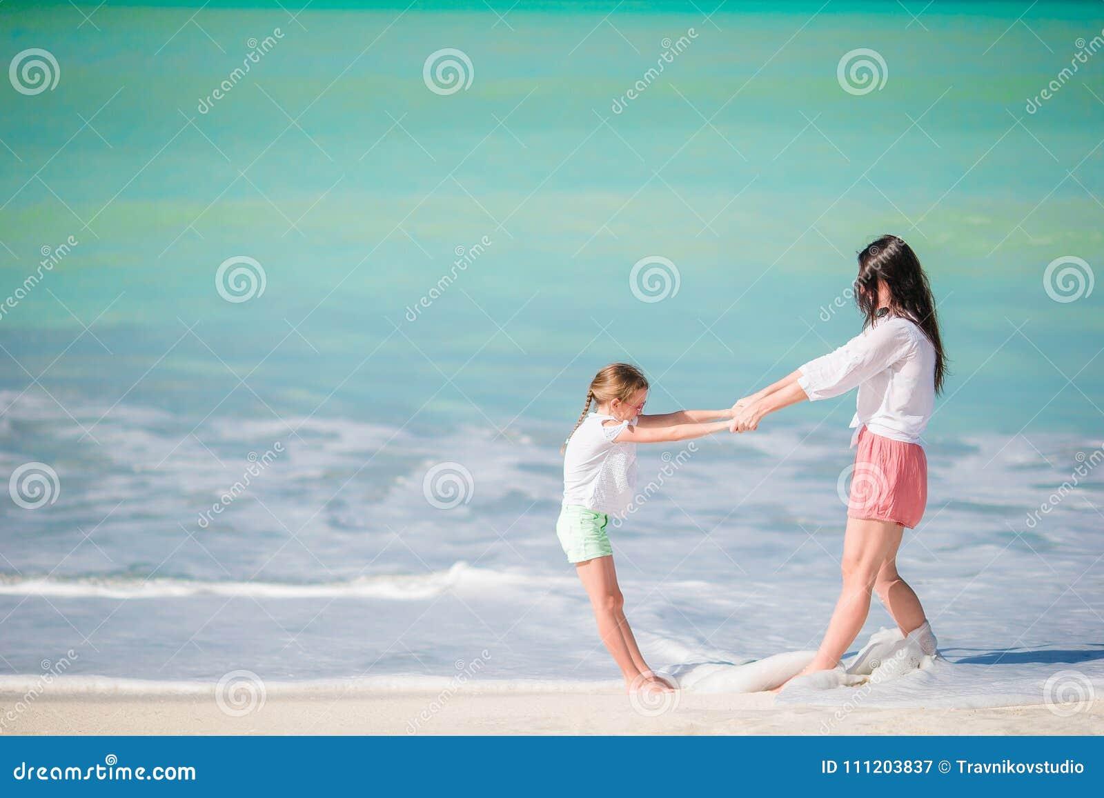 Mooie moeder en dochter die bij Caraïbisch strand de zomer van vakantie genieten Familie die op tropische beroemde heel baai lope