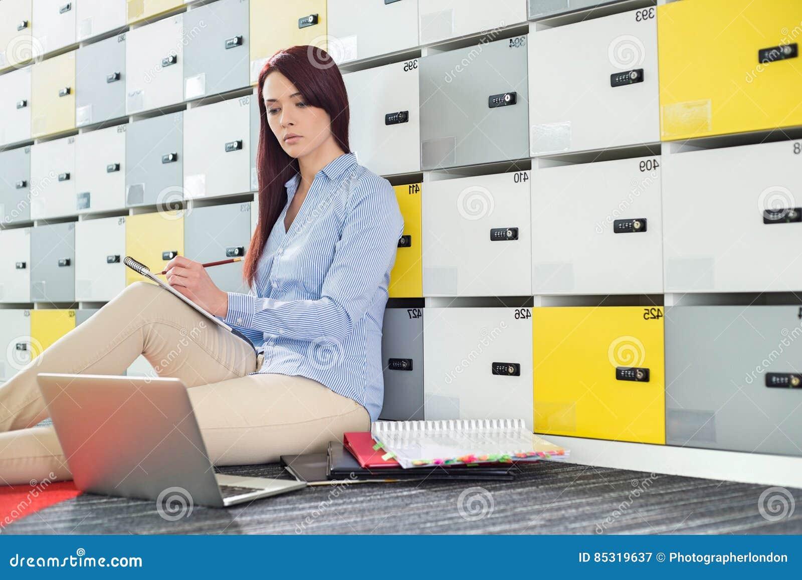 Mooie onderneemster die laptop met behulp van terwijl het schrijven in kleedkamer