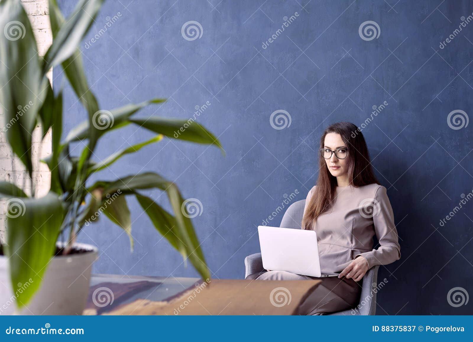 Mooie onderneemster met lang haar die moderne laptop computer met behulp van terwijl het zitten in zijn modern zolderbureau