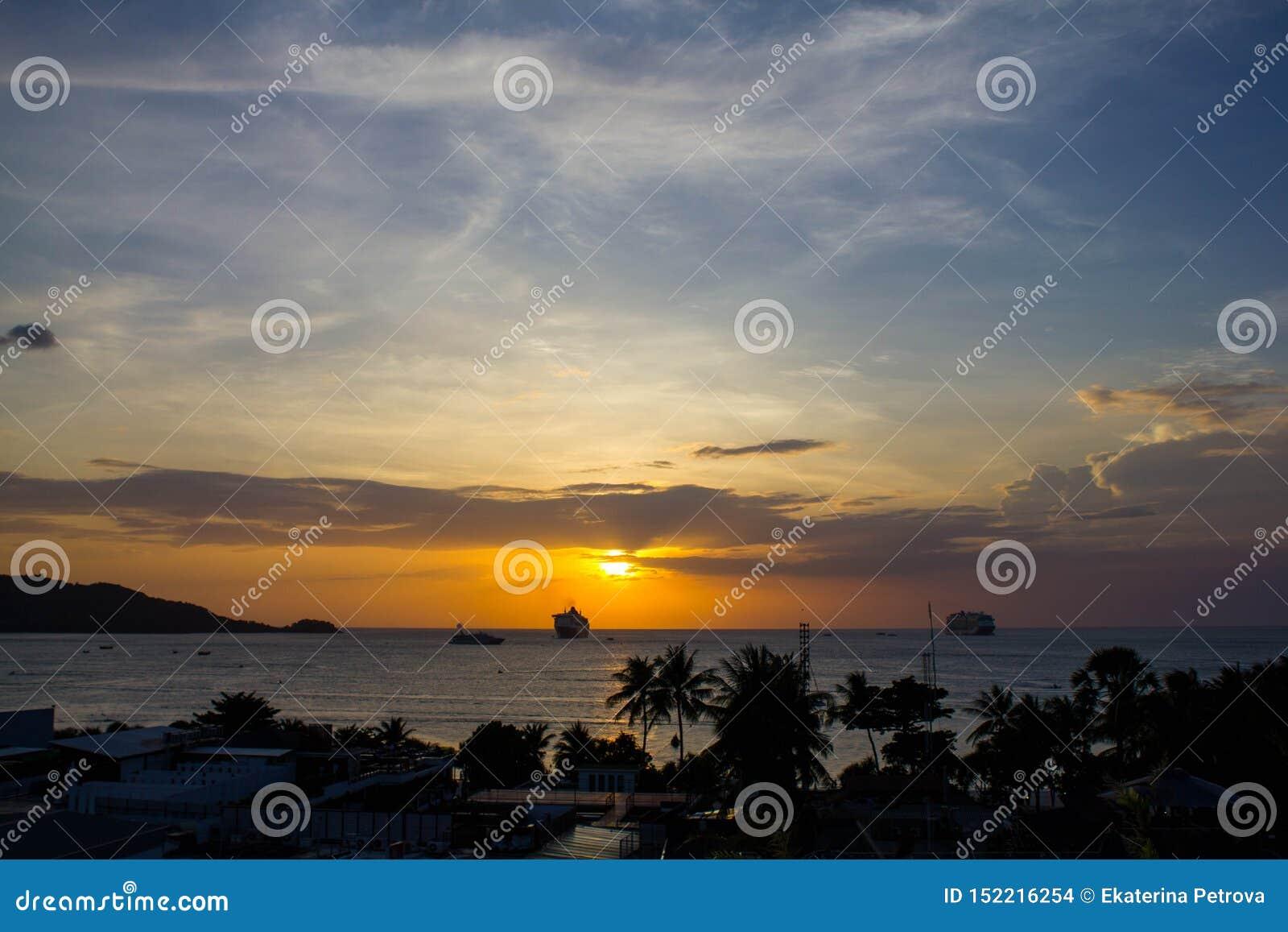 Mooie oranje zonsondergang in het overzees tegen het silhouet van palmen in Thailand Heet de zomerlandschap