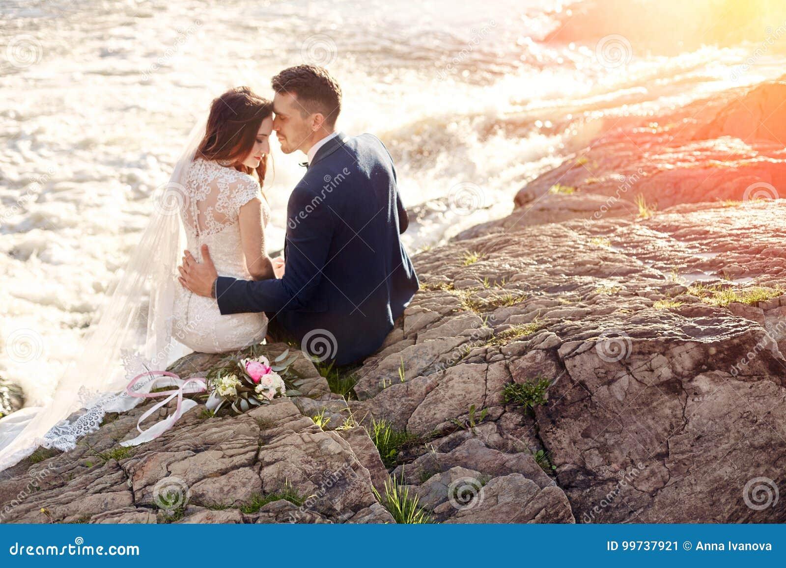 Mooie paarliefde die terwijl het zitten op rotsen dichtbij rivier kussen