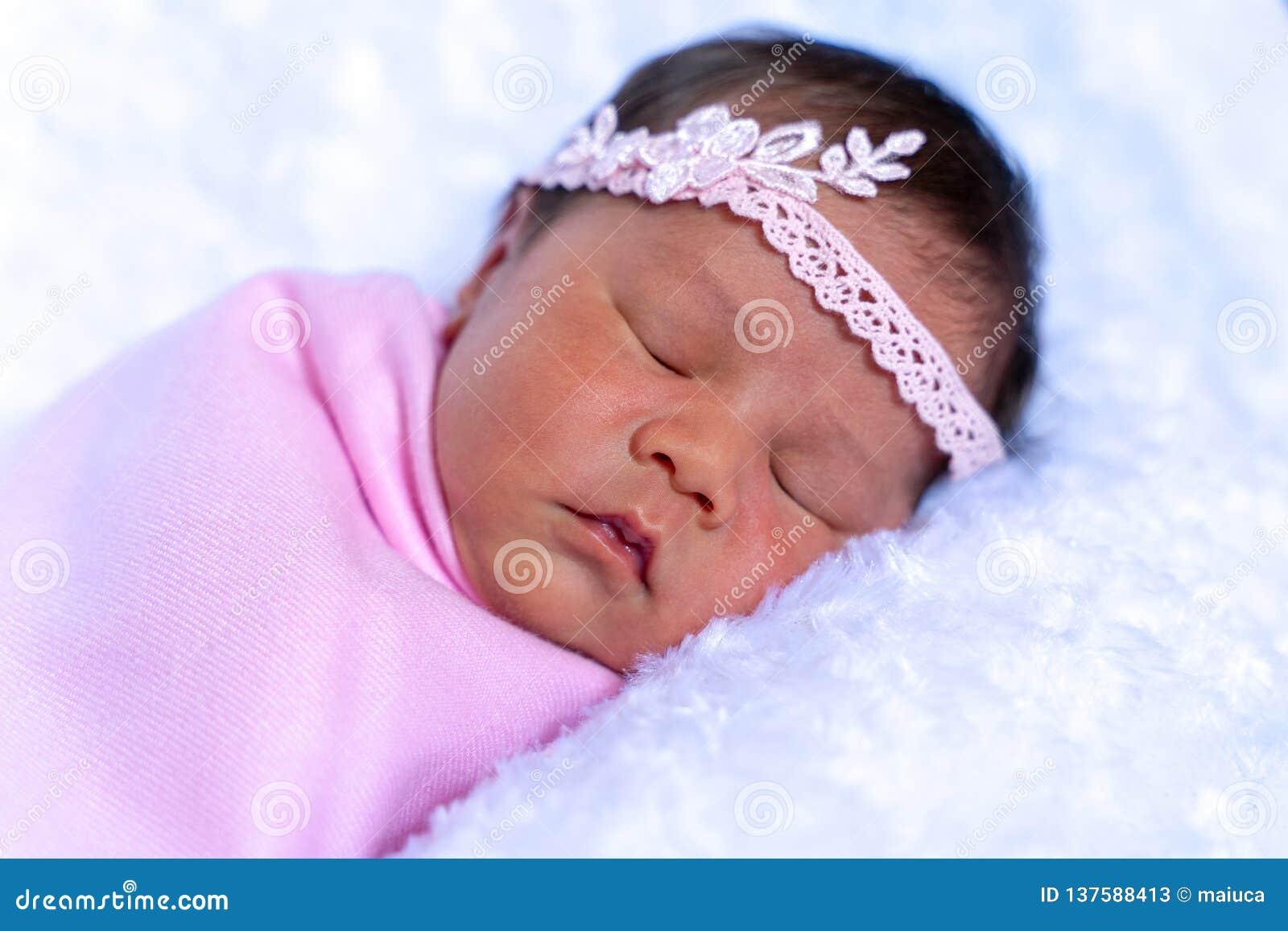Mooie pasgeboren meisjesslaap op witte deken omhoog warpping met lichtrose stof, 6 dagen oude, zachte nadruk