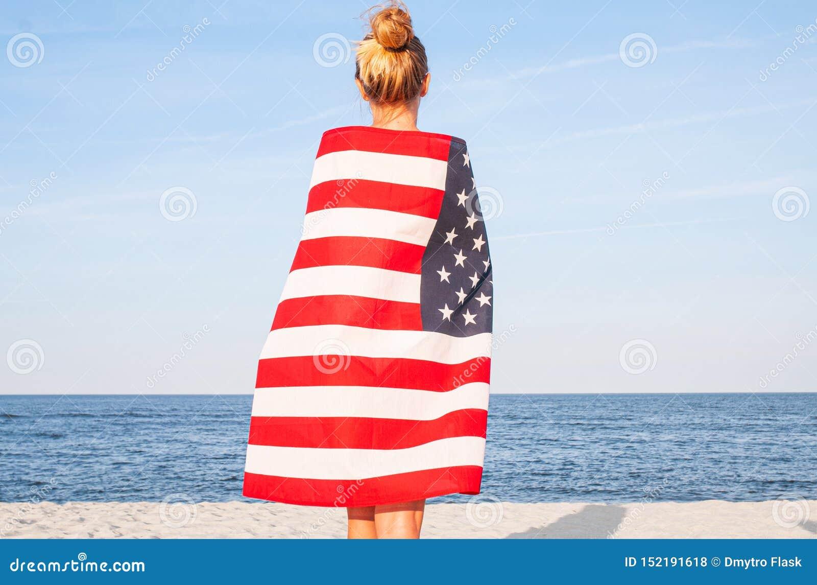 Mooie patriottische vrouw met Amerikaanse vlag op het strand De Onafhankelijkheidsdag van de V.S., 4 Juli Het concept van de vrij