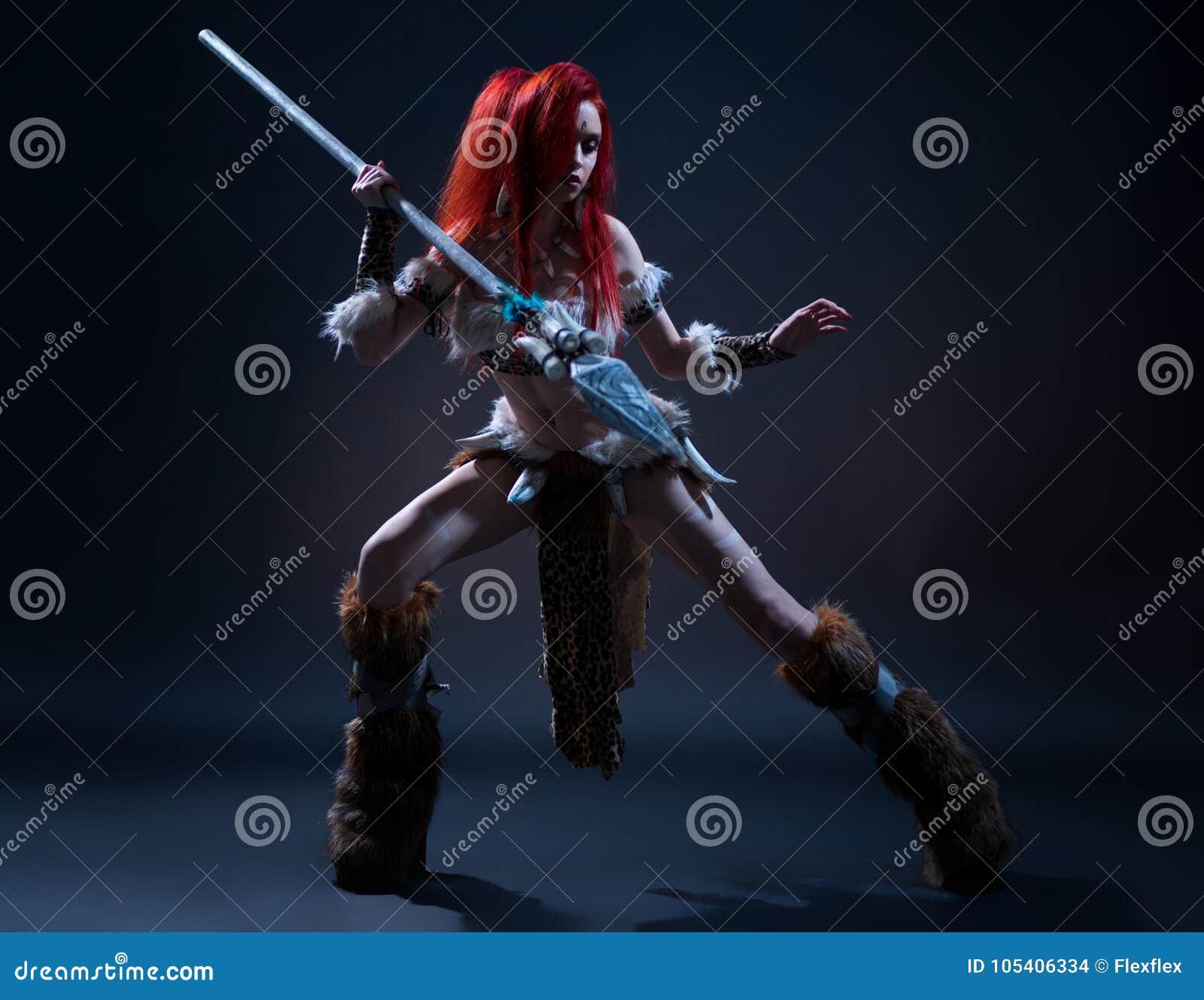 Mooie rode haired vrouw in de kleding van de steenleeftijd