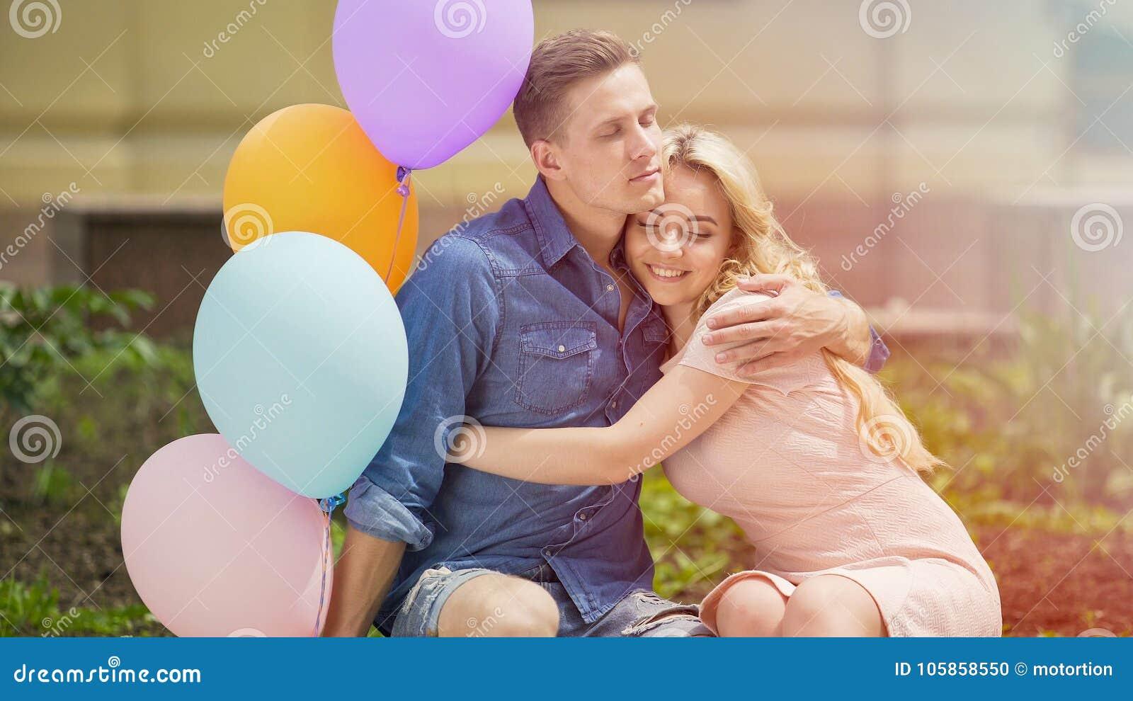 Mooie romantische paar het vieren verjaardag, die op bank in park koesteren