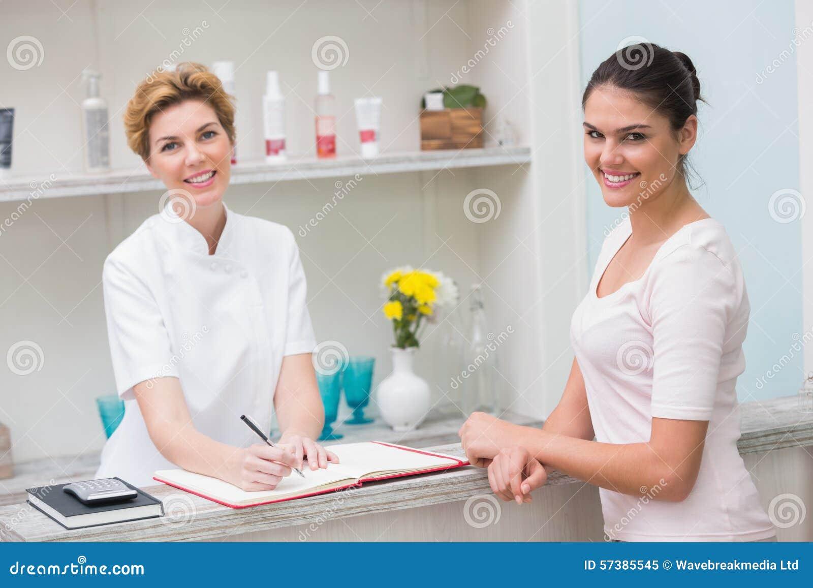 Mooie schoonheidsspecialist die met cliënt glimlachen