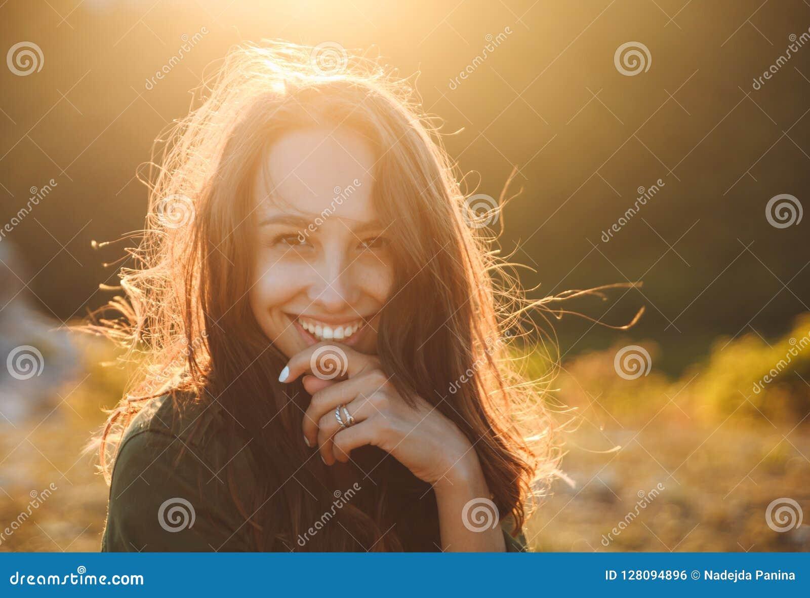 Mooie sexy jonge vrouw die op mooi landschap in zonsondergangtijd glimlachen