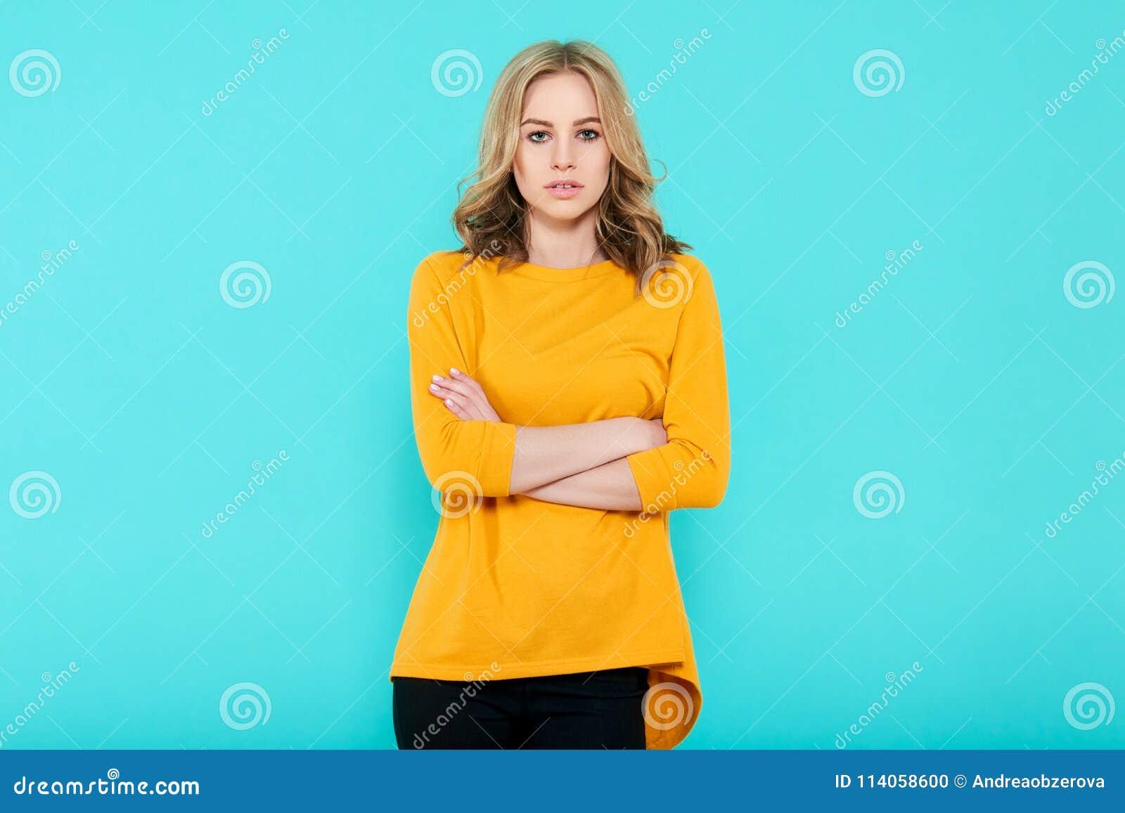 Mooie sexy jonge vrouw in helder geel hoogste studioportret op pastelkleur blauwe achtergrond Aantrekkelijke vrouw met gekruiste