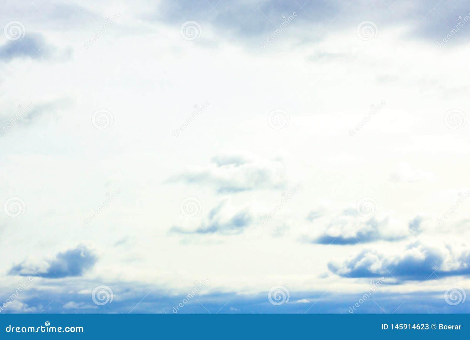 Mooie sombere blauwe hemel met pluizige wolken in de vredesdag van de de zomerochtend als achtergrond