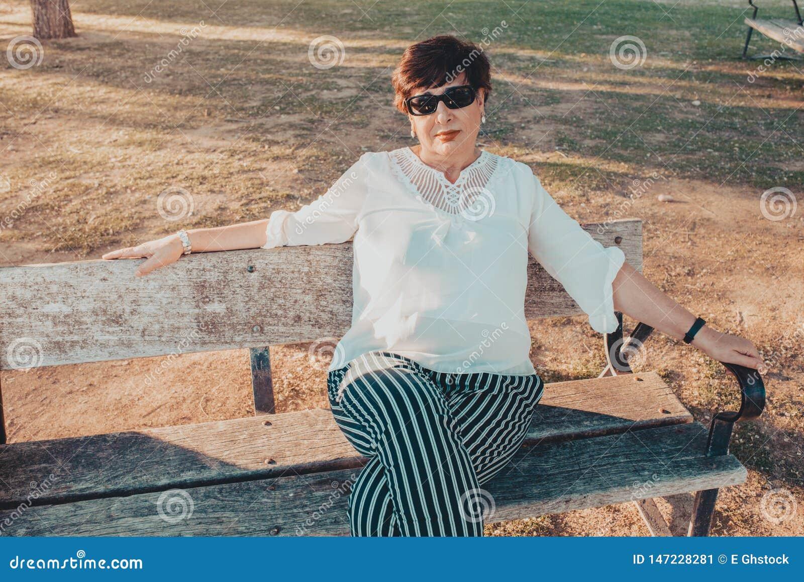 Mooie Spaanse midden oude vrouw in de parkzitting op een bank bij zonsondergang