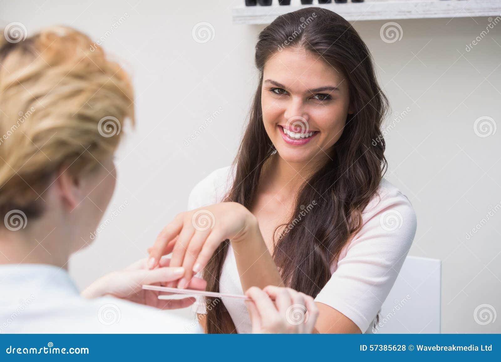 Mooie spijkertechnicus die manicure geven aan klant