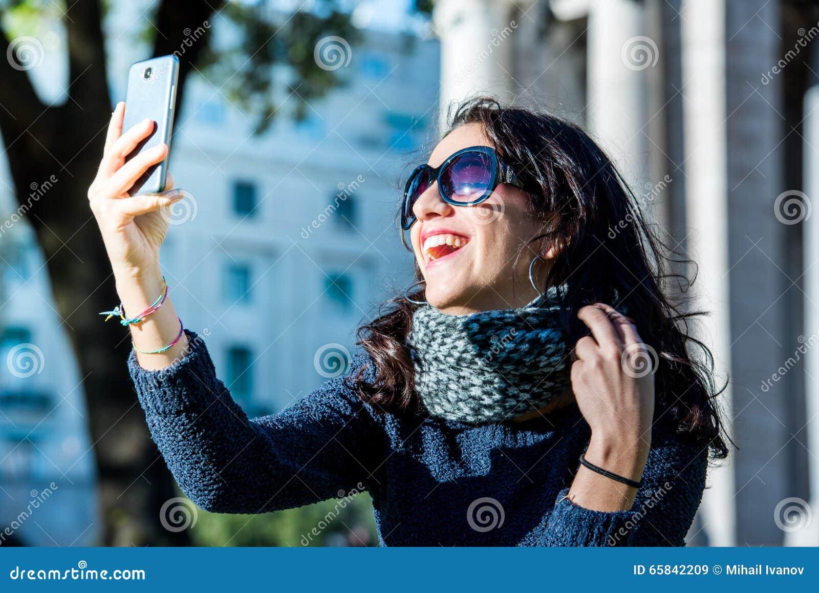 Mooie tiener met donkere haar en zon selfies en glazen die nemen laughting - sluit schot