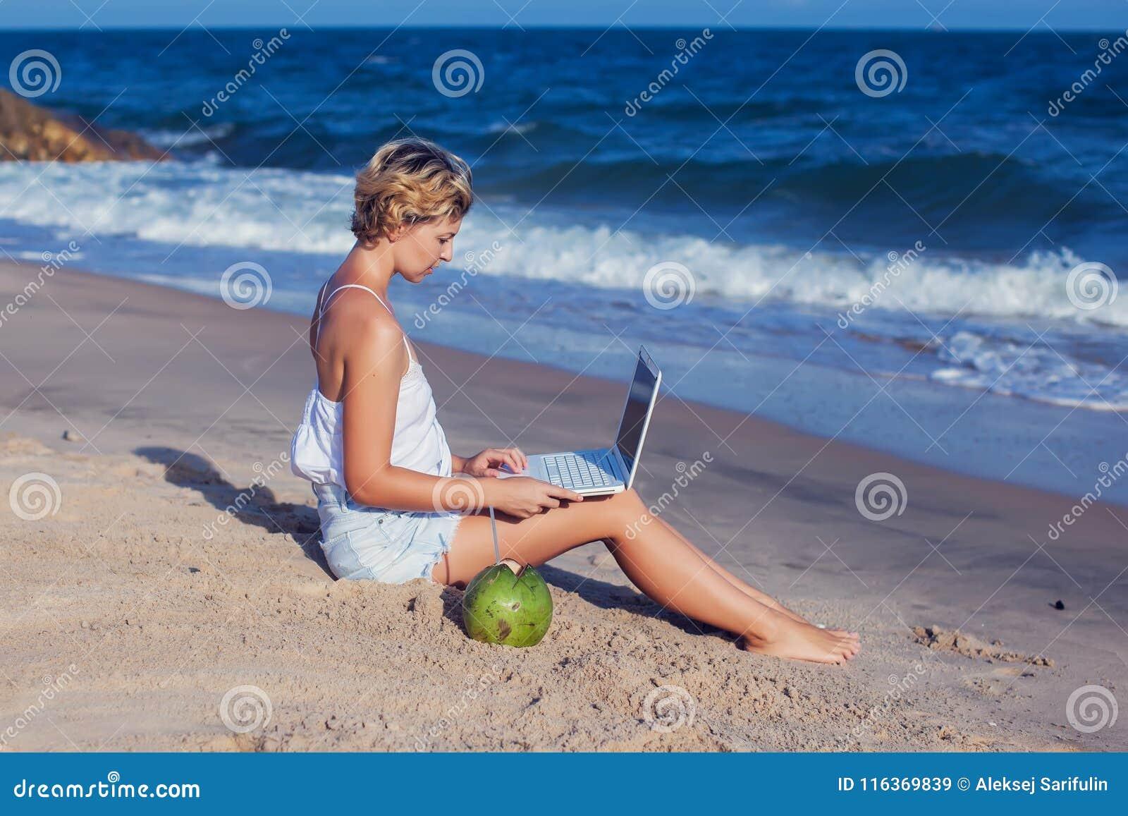 Mooie toevallige vrouw met laptop op het strand met overzees i