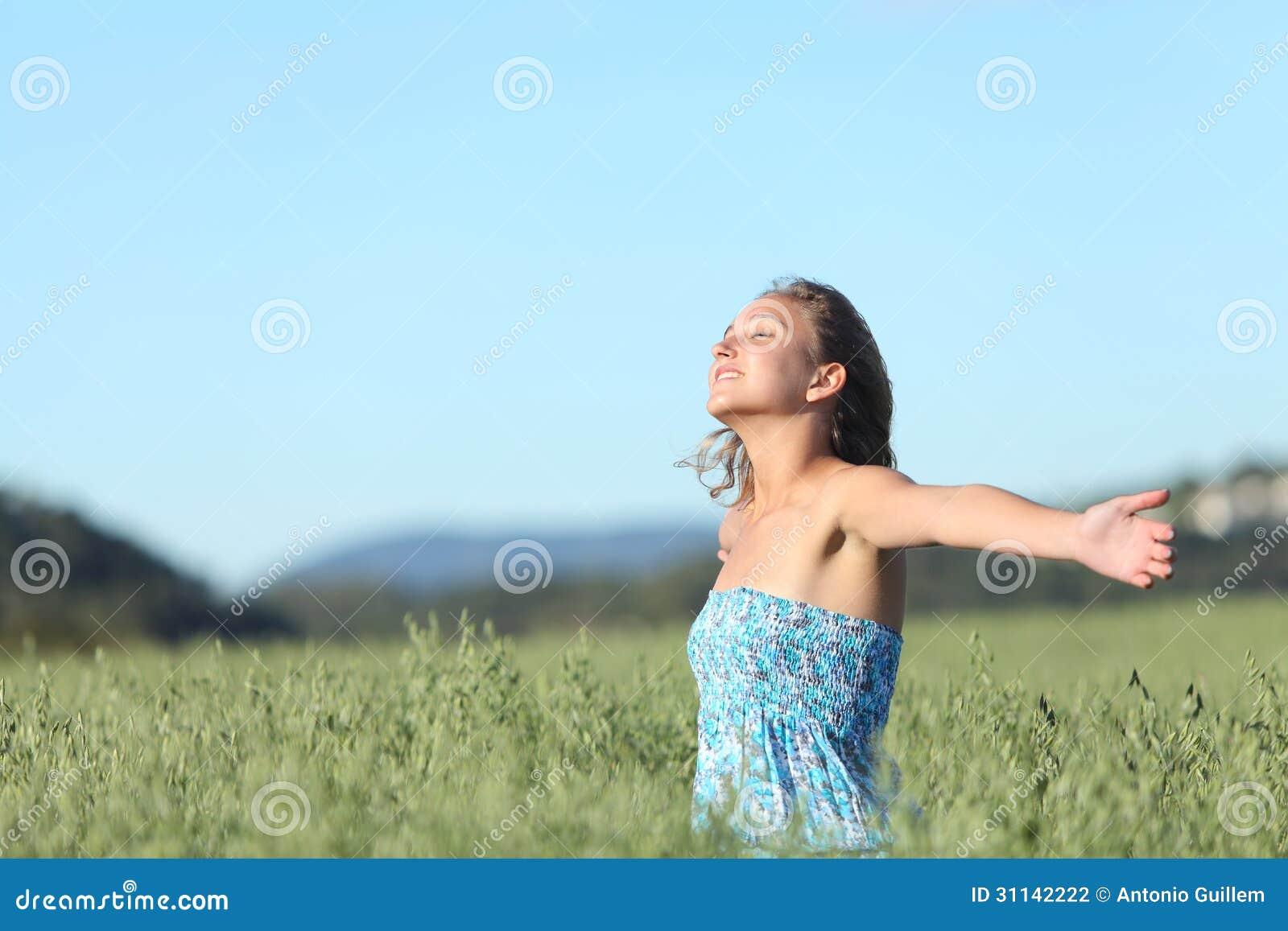Mooie vrouw ademhaling gelukkig met opgeheven wapens in een groene haverweide