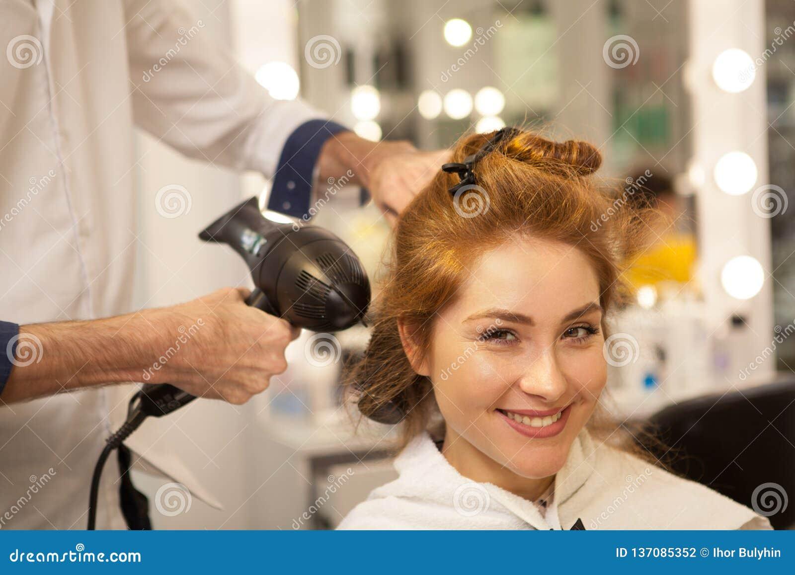 Mooie vrouw bij de salon van de haarschoonheid