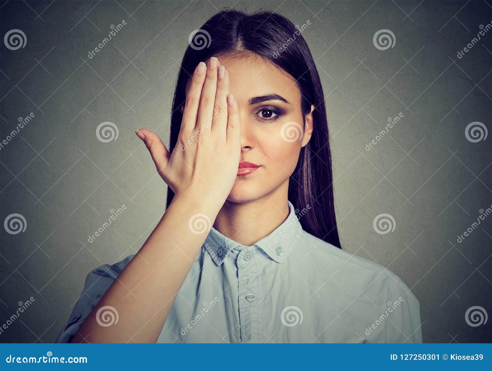 Mooie vrouw die één oog behandelen met hand