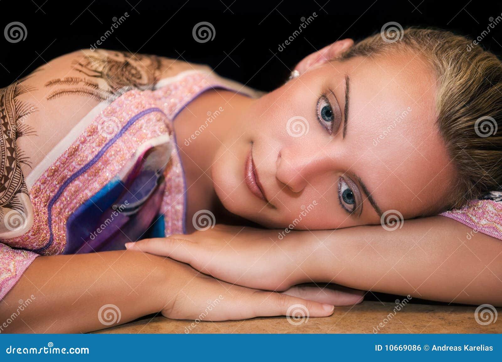 Mooie vrouw die bij haar wapens en het denken rust