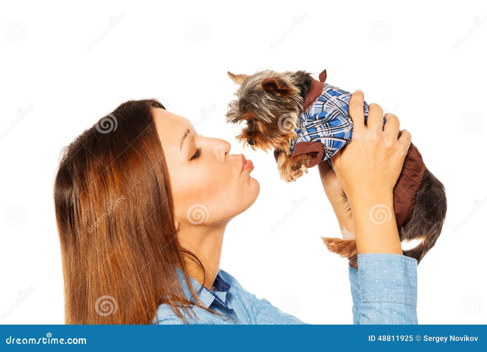 Mooie vrouw die bruin Yorkshire Terrier kussen