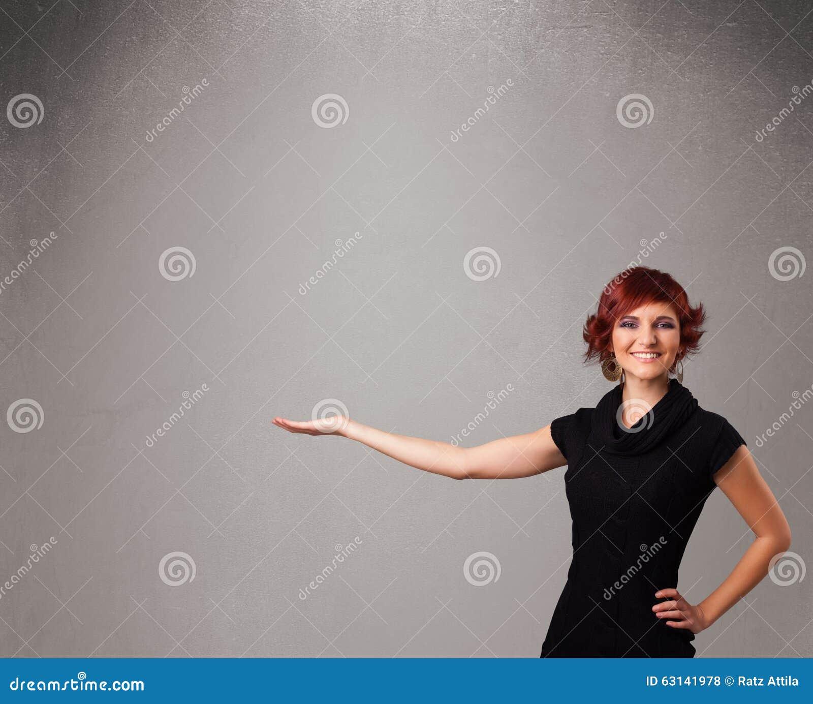 Mooie vrouw die een lege exemplaarruimte voorstellen