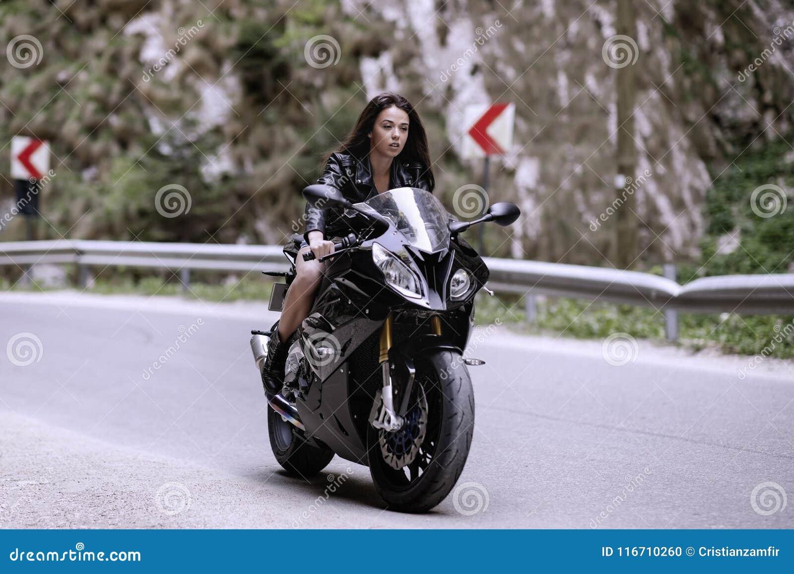 Mooie vrouw die een motorfiets drijven