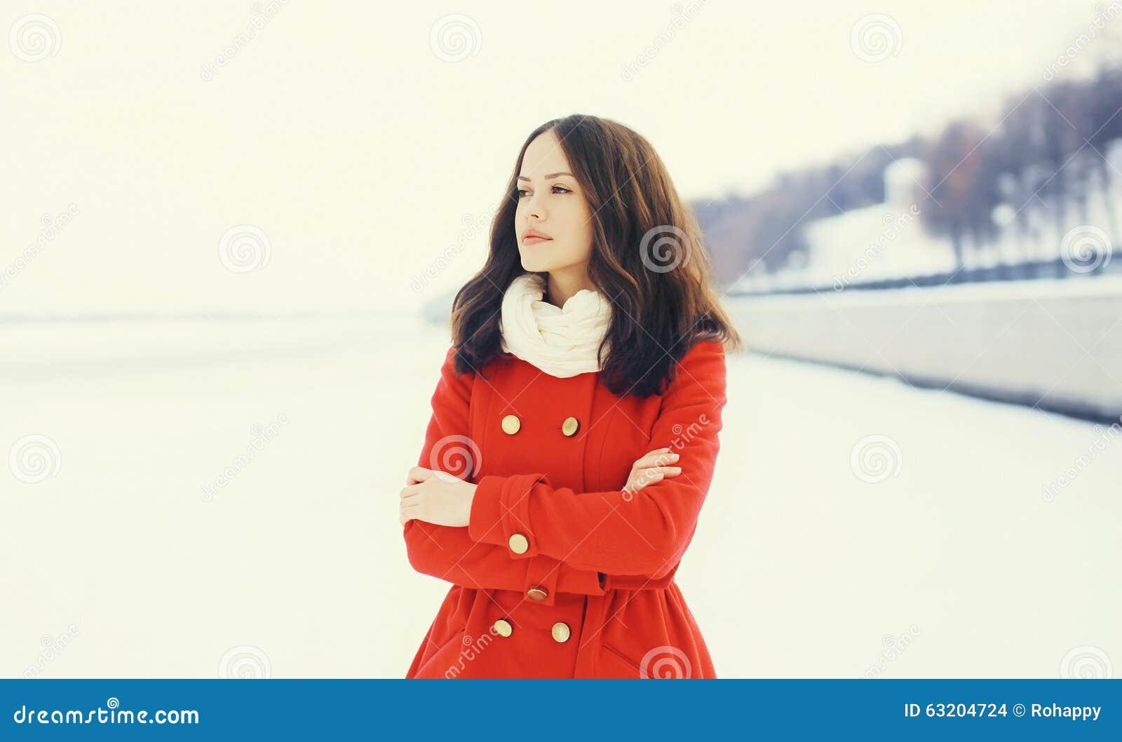 Mooie vrouw die een rode laag en een sjaal over sneeuw in de winter dragen