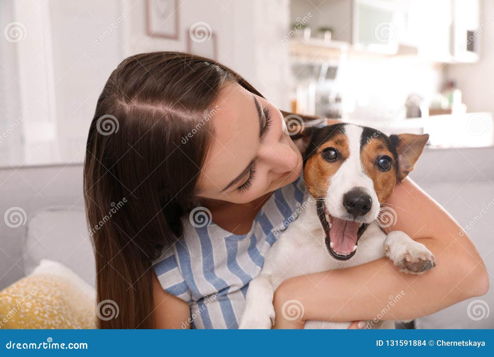 Mooie vrouw die haar hond op bank koesteren
