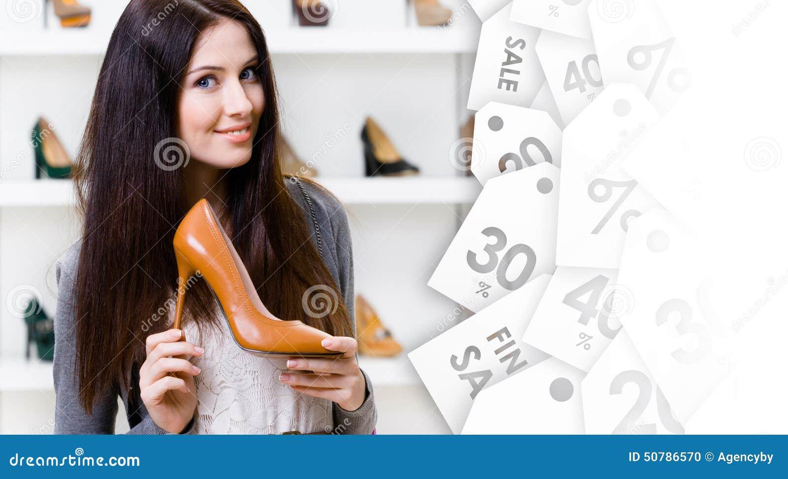 Mooie vrouw die hoog gehielde schoen op uitverkoop houden