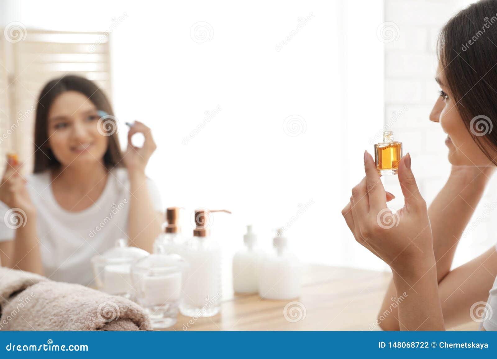 Mooie vrouw die olie op haar wimpers toepassen dichtbij spiegel