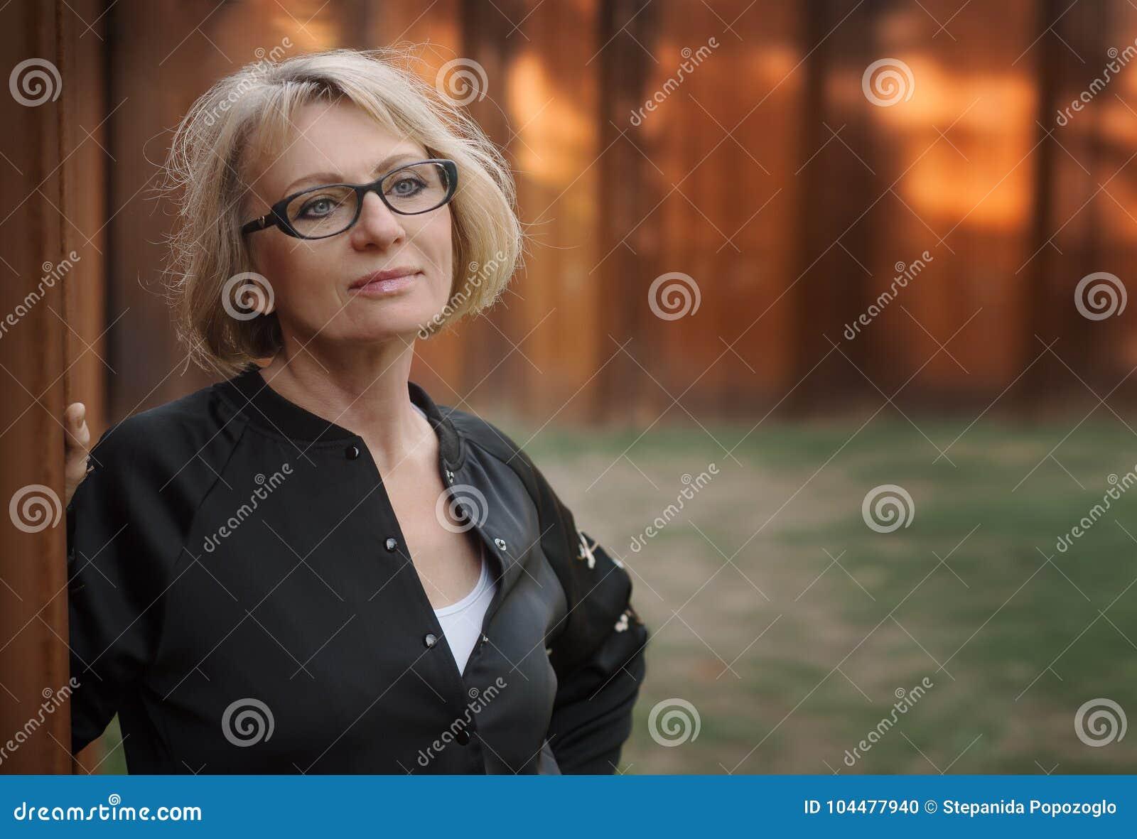 Mooie vrouw die op middelbare leeftijd zich door de muur in het park bevinden Ph