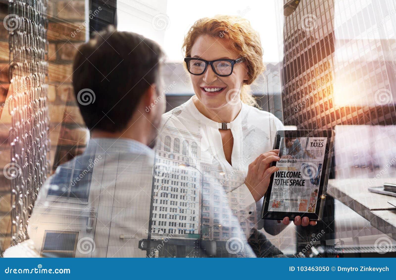 Mooie vrouw die tablet met nieuwsartikel tonen aan haar werkgever