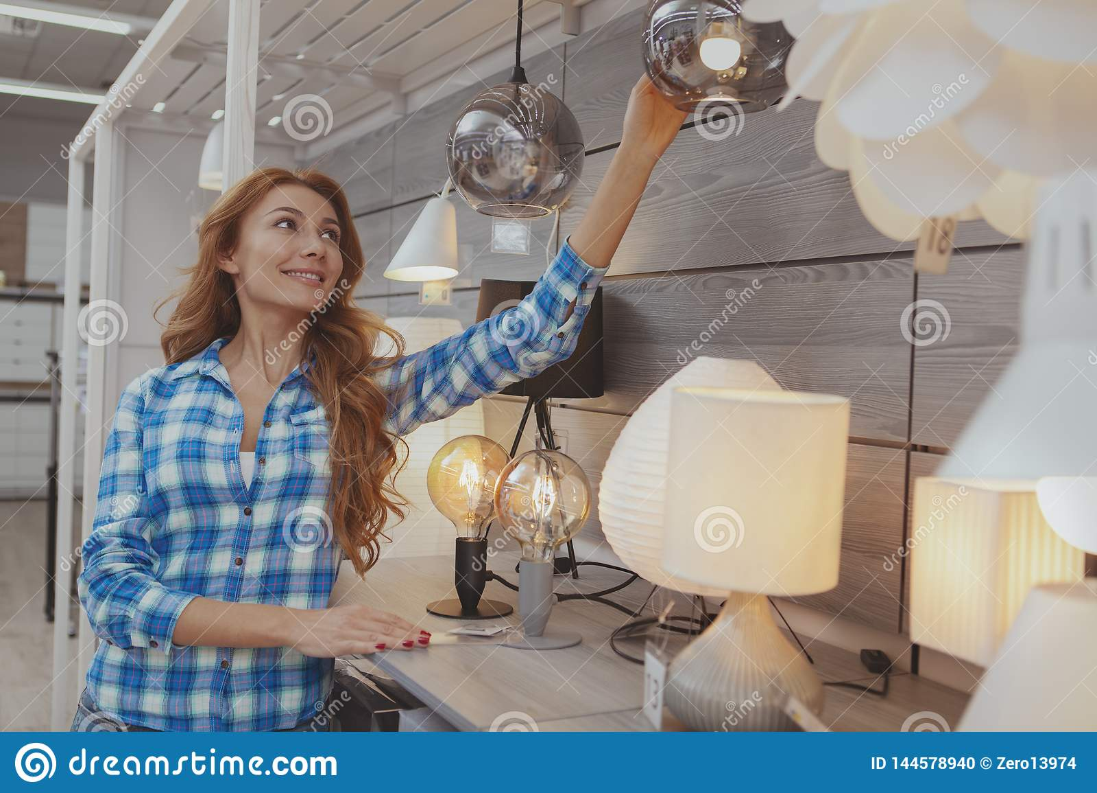 Mooie vrouw die voor milieuvriendelijke verlichting winkelt