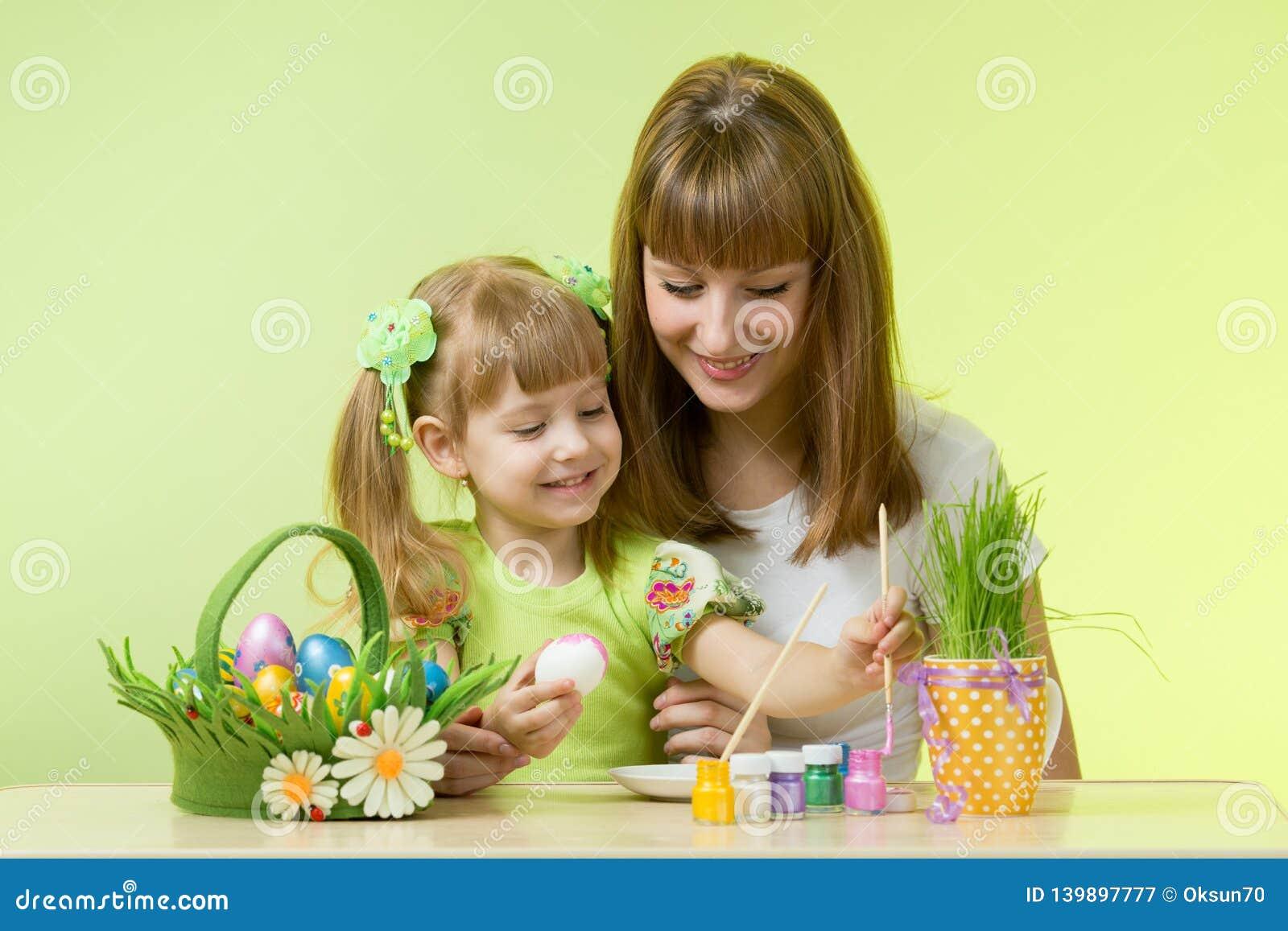 Mooie vrouw en haar dochter die paaseieren kleuren bij de lijst