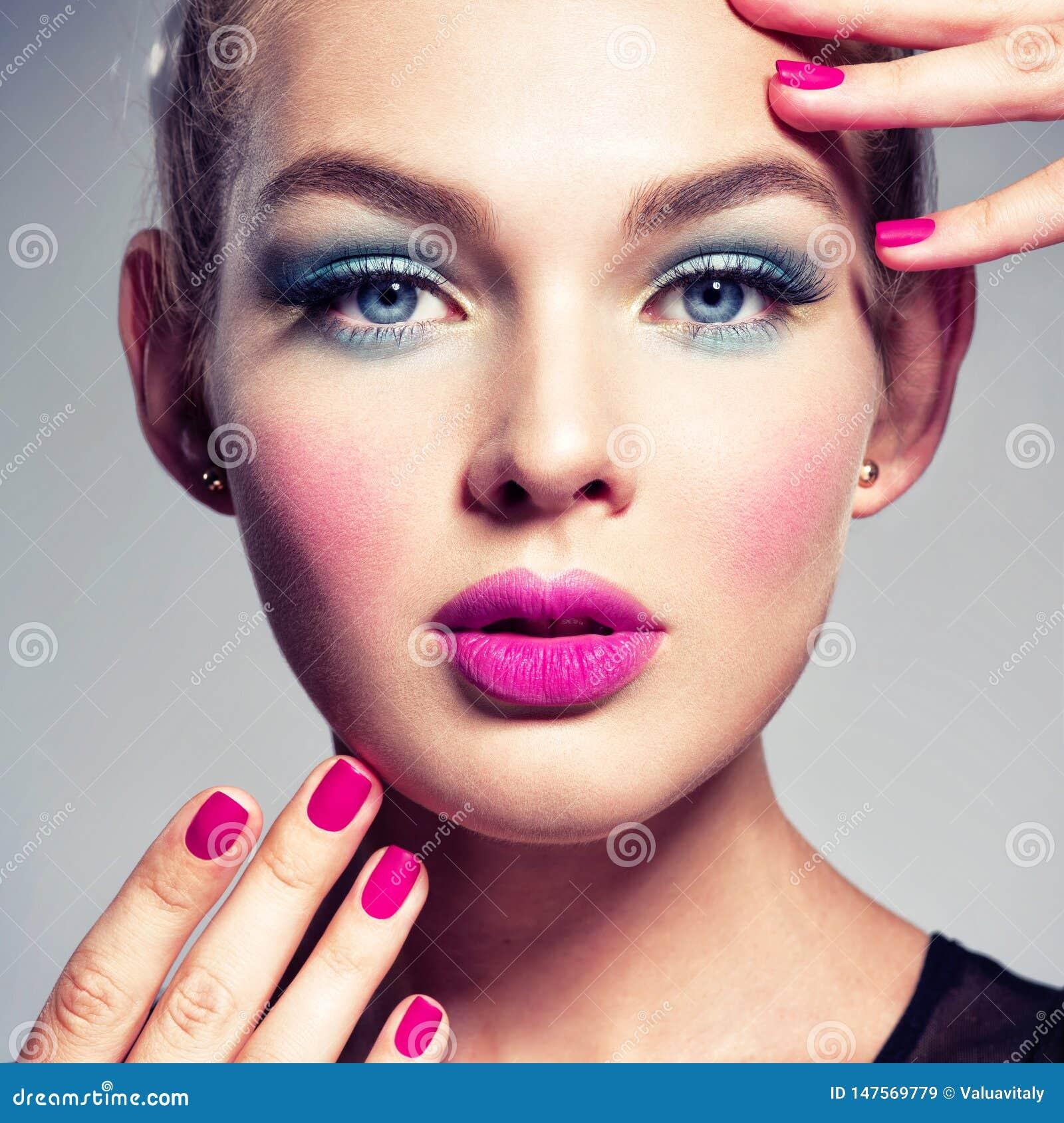 Mooie vrouw met blauwe make-up van ogen en roze spijkers