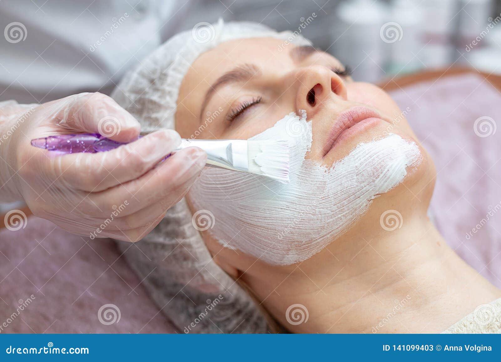 Mooie vrouw met een gezichtsmasker bij een schoonheidssalon