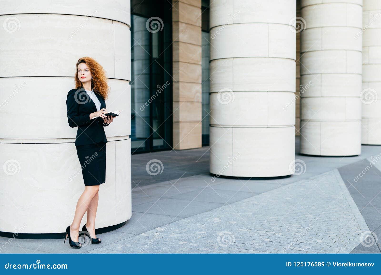 Mooie vrouw met krullend haar, slanke benen, die zwart kostuum en high-heeled schoenen dragen, houdend notitieboekje in handen, d