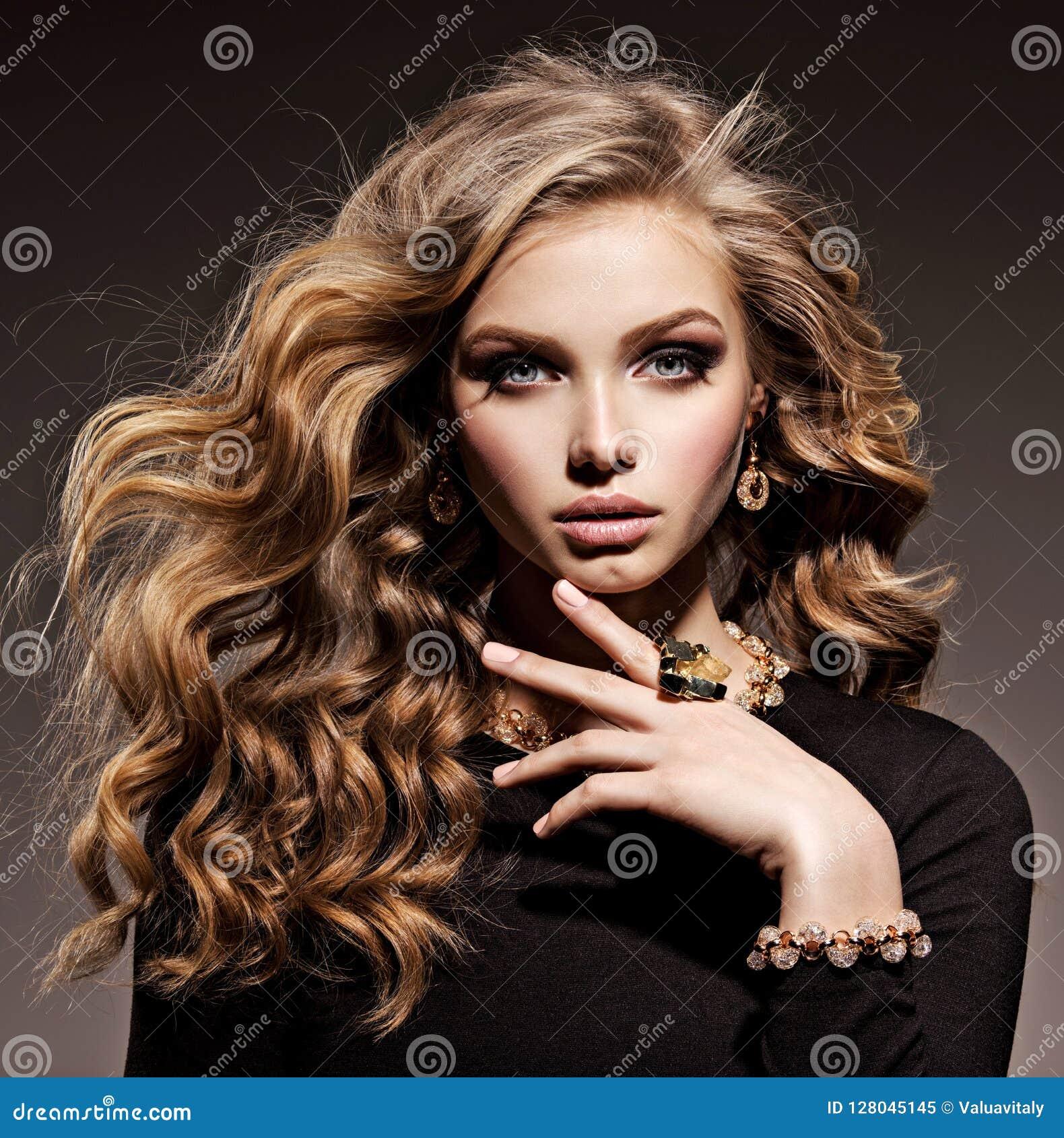 Mooie vrouw met lang krullend haar en gouden juwelen