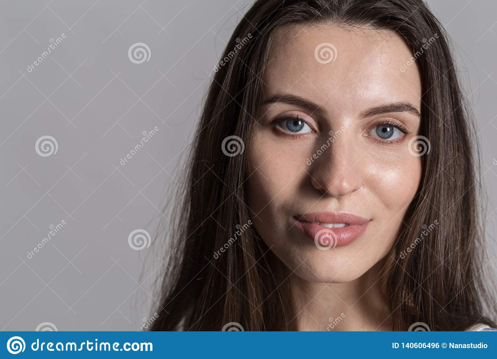 Mooie vrouw met pluizig haar, terloops gekleed tegen een grijze studiomuur