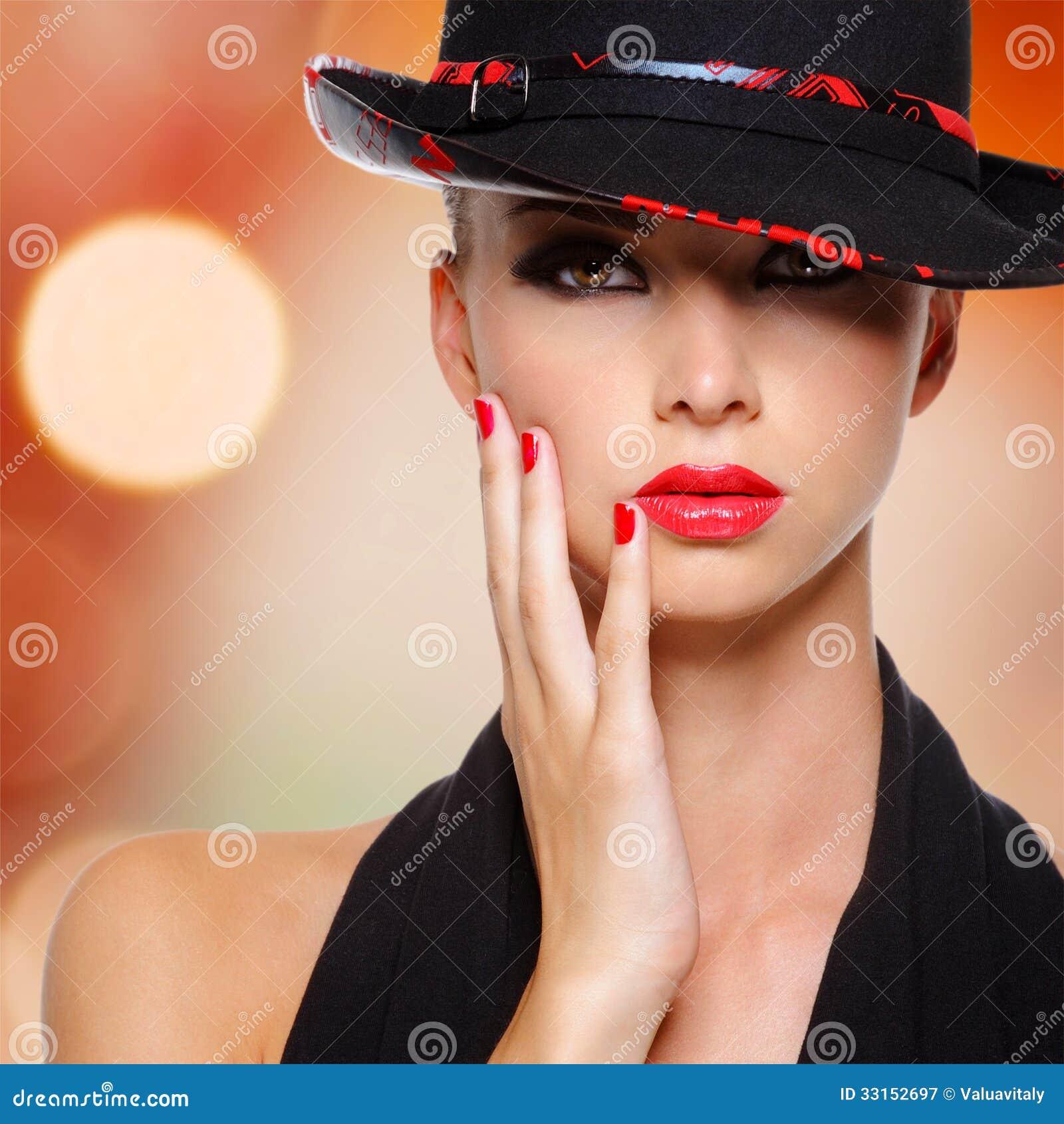 Mooie vrouw met rode lippen en spijkers in zwarte hoed