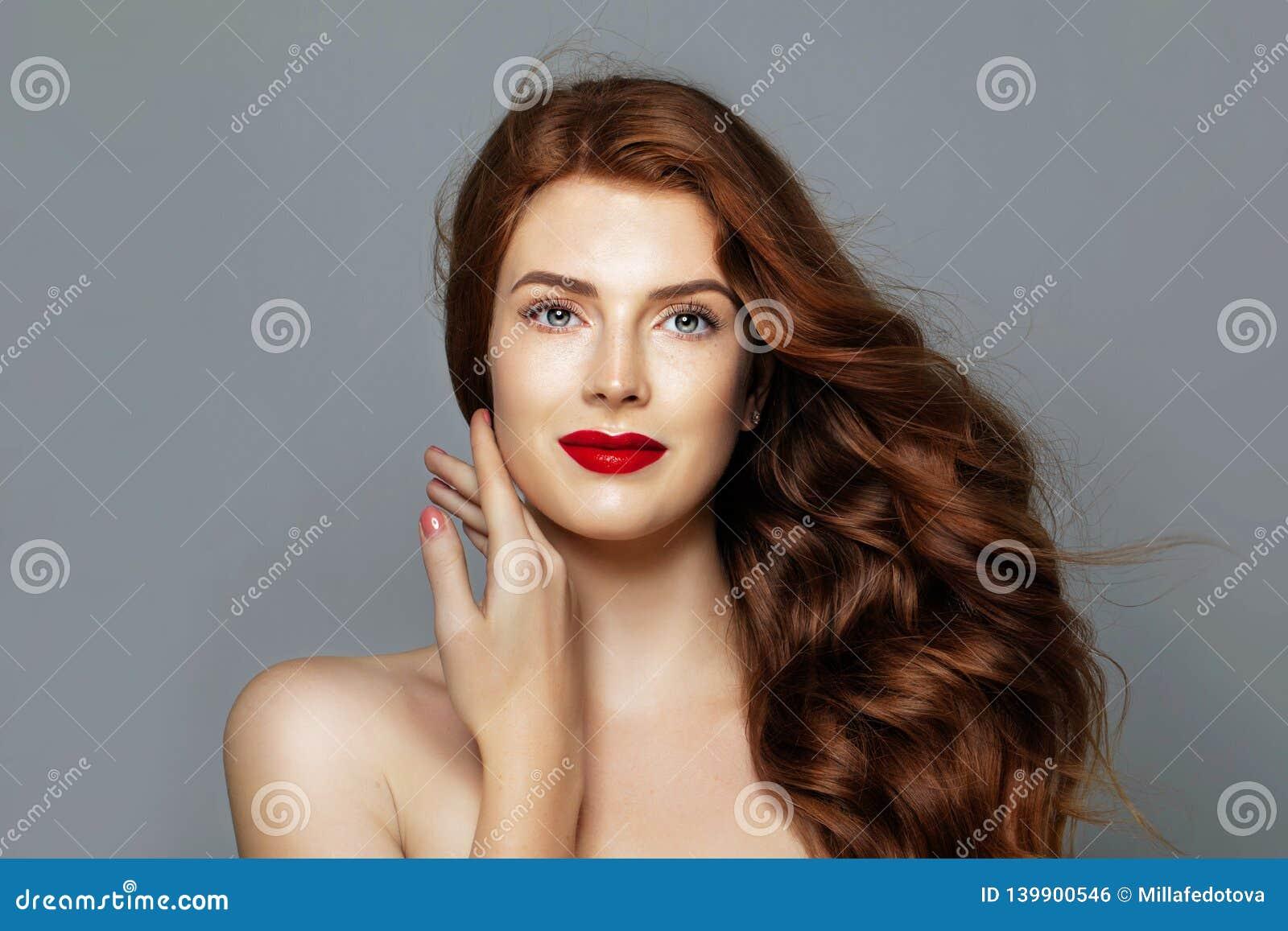 Mooie vrouw met rood krullend haar Vrolijk roodharigemodel op blauw portret als achtergrond
