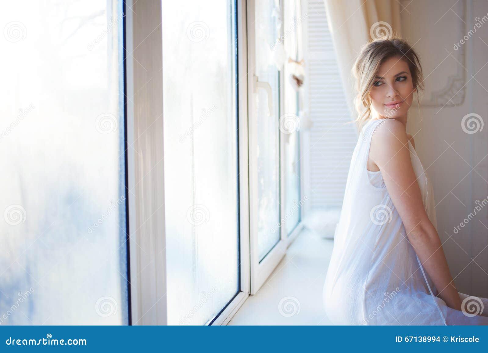 Mooie vrouw met verse dagelijkse make-up en romantisch golvend kapsel, die bij de vensterbank zitten