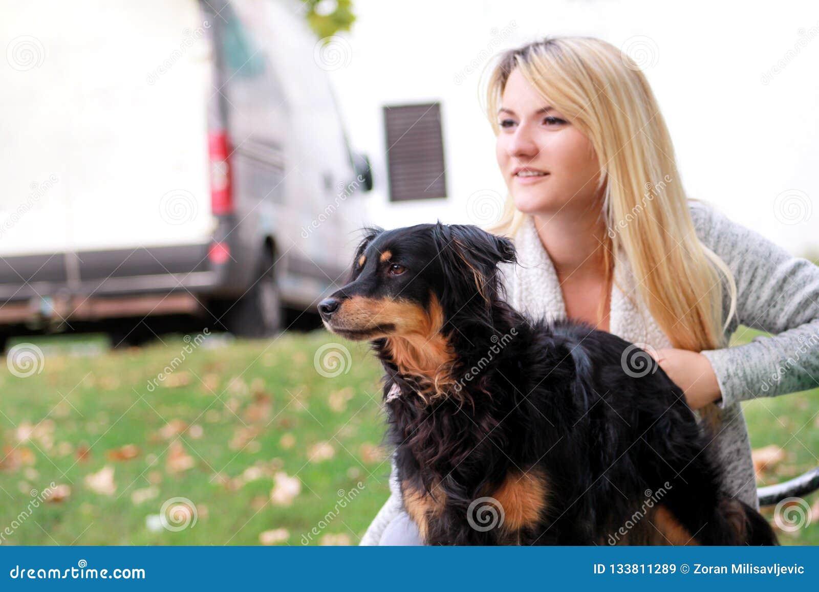 Mooie vrouw met zijn kleine gemengde rassenhond zitting en het stellen voor camera op houten bank bij stadspark