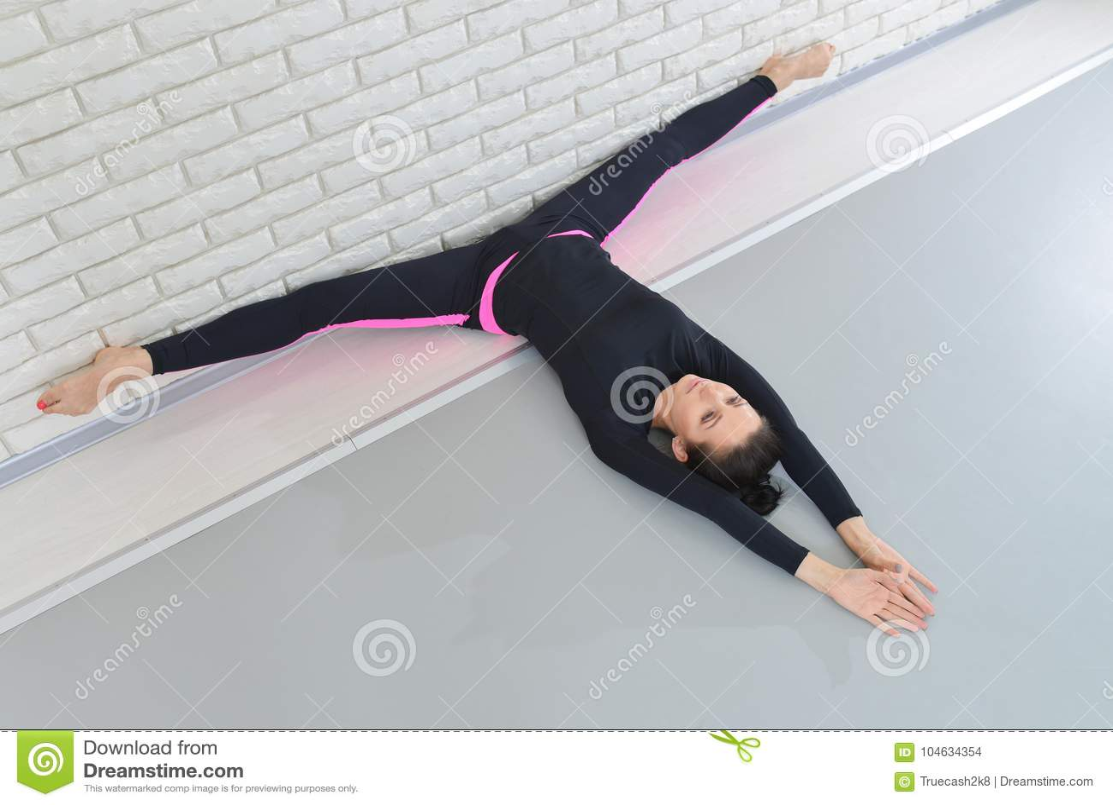 Download Mooie Vrouw In Sportkleding Die Bij Geschiktheidsstudio Uitoefenen, Die Streng Uitvoeren Die Op De Vloer Dichtbij Muur Liggen Hog Stock Foto - Afbeelding bestaande uit lichaam, lying: 104634354