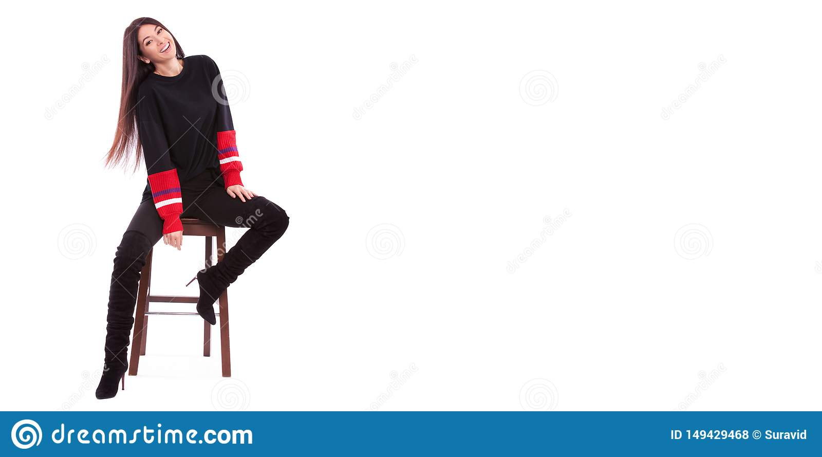 Mooie vrouw in zwart die kostuum op witte achtergrond wordt ge?soleerd Het leuke brunette zit op de stoel bij witte studio Sluit