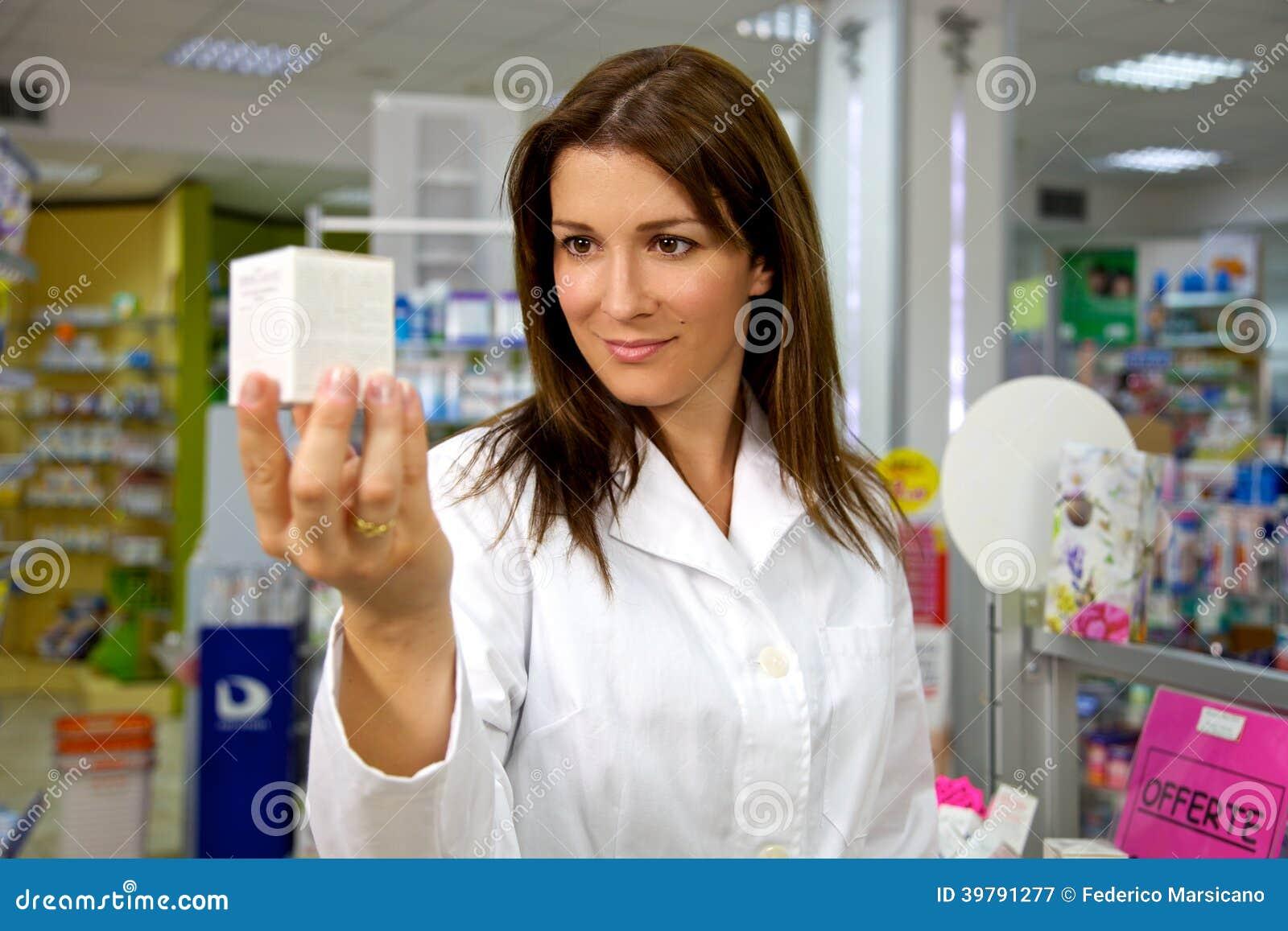 Mooie vrouwelijke arts in eenvormige holdingsgeneeskunde in apotheek het glimlachen