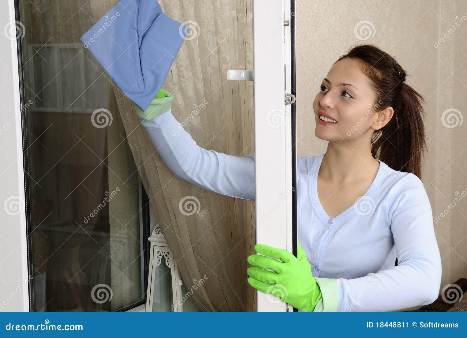 Mooie vrouwen die een venster schoonmaken