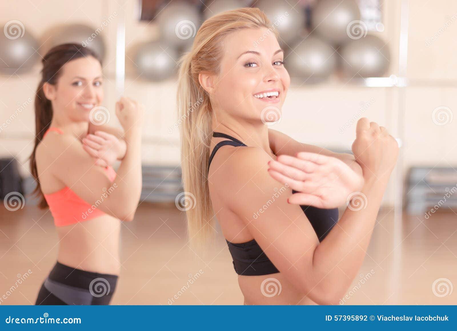 Mooie vrouwen die oefeningen in gymnastiek doen